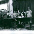Hussein bin Talal sitting on chair, people standing beside.  - 8x10 photo