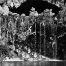 Audrey Hepburn standing wearing a hat under the waterfall. - 8x10 photo