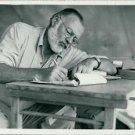 The author Ernest Hemingway writing.   - 8x10 photo