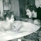 Brigitte Bardot bathing in milk in bathing tub and Alberto Sordi talking to her.