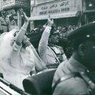 Hussein bin Talal with his wife sitting inside the car, waving.  - 8x10 photo