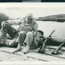 Ernest Hemingway relaxing on the lakeshore with a child and two rifles. - 8x10 p