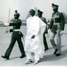 Shehu Usman Aliyu Shagari, walking, security guard around him.  - 8x10 photo
