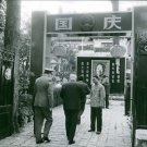 A VIP entering a property in China that has the image of Mao Zedong erected at t