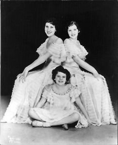 Judy Garland, sitting, with her sisters, known as the Gumm sisters. - 8x10 photo