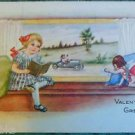 YOUNG GIRL READING CUPID POINT-VINTAGE EMBOSSED WHITNEY MADE VALENTINE POSTCARD
