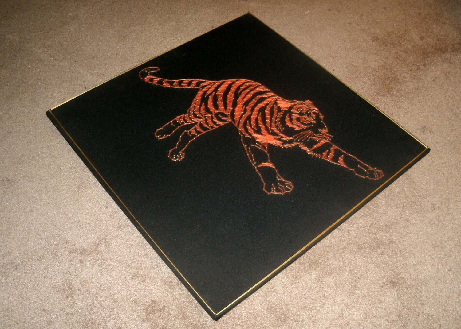 String Art/A Tiger Running/on black velvet/.