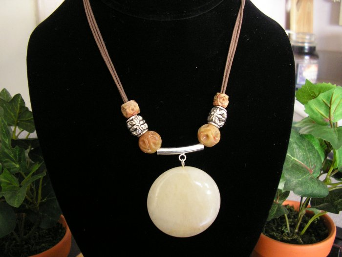 Milky quartz pendent on a brown cotton cord with pewter and soapstone beads .