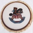 Finished completed cross stitch bear on rocking horse 10 inch round