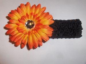 Orange 4 inch Gerbera Daisy hair clip on a black 1.5 inch crochet headband