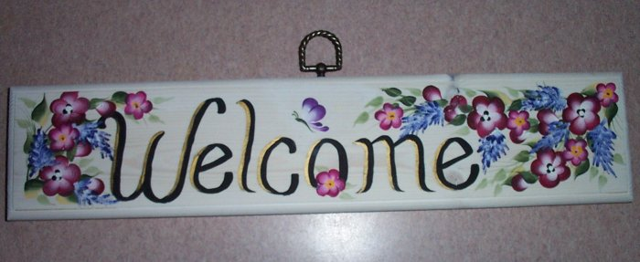 welcome sign with small burgundy & purple flowers