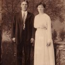 1916 Portrait of Couple Standing in Front of Scenic Backdrop, Real Photo Post Card RPPC - 2923