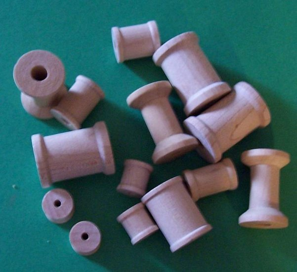 Lot of ten new wooden spools in assorted sizes