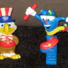 Olympic Games PVC Figure Lot of 2 Izzy Sam the Eagle Atlanta Los Angeles Torch Track and Field