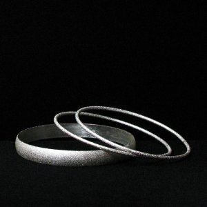 pebbly silvertone fireworks bangles - vintage jewelry