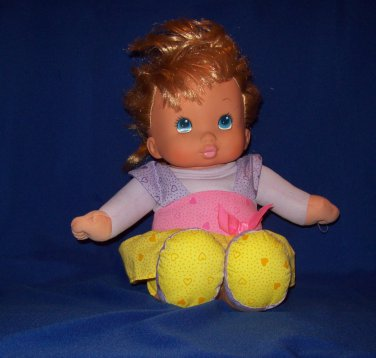 Baby doll, purple, pink and yellow dress, vinyl head, soft cloth body and arms and legs.