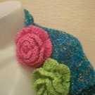 Knitted  shrug in Turquoise with pink and green flowers on it.M size