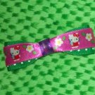 Green polka dot and hello kitty bow super cute with snap clip on back