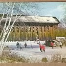 PEOPLE ICE SKATING BELOW A NEW ENGLAND COVERED BRIDGE POSTCARD