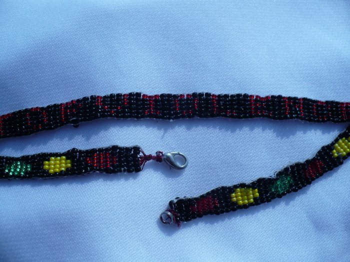 "choker with red yellow and green circles on a black background.Spells out ""stop violence"" in red"