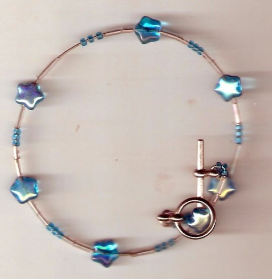 bracelet made of blue glass star shaped beads seed beads and bugle beads on memory wire.