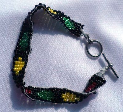 Bracelet with red yellow and green circles on a black background made of seed beads.