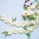 Hand-crochetted white peachblossom flowers scar f with green leaves