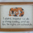 Orange calico cat on lazy day schedule completed cross stitch