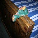 dragon statue hangs over shelf etc.
