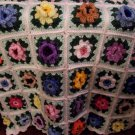 Mulit Colored Flowery Granny Square Afghan on White Background with pillow