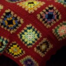 Multi Colored Granny Square Afghan on Rusty Colored Background