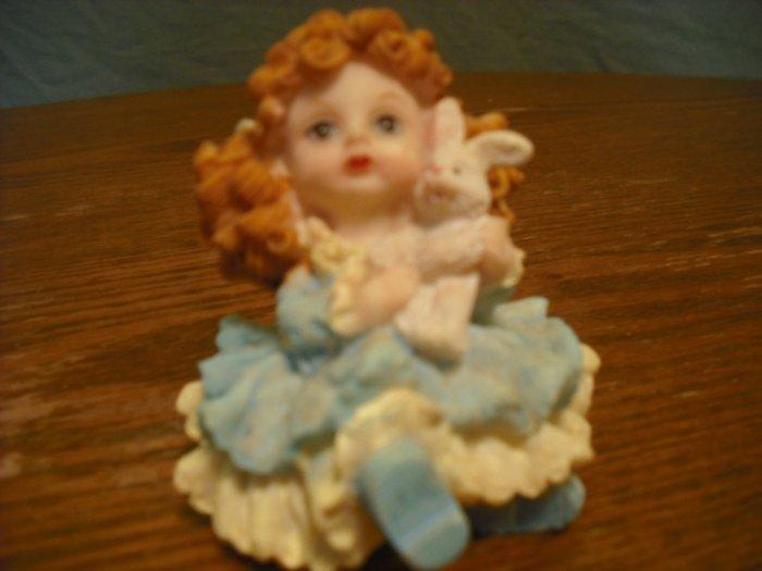 little girl with bunny figurine