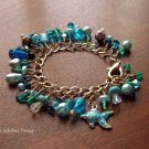 Handmade light blue and teal glass bead and tropical fish charm bracelet