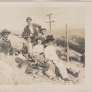 Vintage Postcard Family Sitting on grassy bank  early 1900's