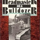HEADMASTER ON A BULDOZER BUILDING A SCHOOL FROM THE GRO