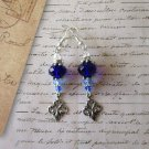 Deep Blue Faceted Crystal and Fleur de Lys Stamping Charm Silver Tone Earrings.