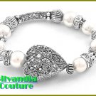Designer inspired bracelet flaunts a silver finish, detailed heart with white faux pearls.