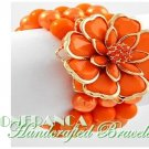 JONFRANCA fashion bracelet featuring orange Paramount® acrylic flowers and pearls.