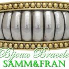 A two-tone tapered hinge designer metal bracelet that broadcasts a polished ball texture.