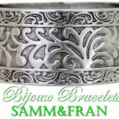 Womens bracelet is crafted with filigree texture, satin silvertone finish and hinged design.