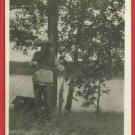 RPPC MAN FISHING W/FISH ON STRINGER  LARGE BRIMMED HAT