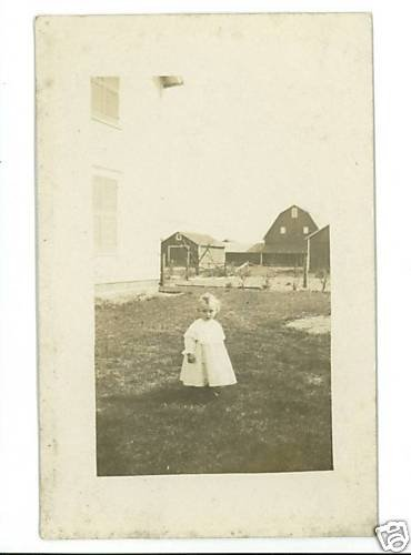 RPPC ADORABLE LITTLE GIRL IN YARD WITH  BARN  & HOUSE