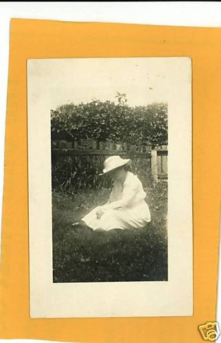 WOMAN SITTING IN GRASS REAL PHOTO POSTCARD WOOD FENCE