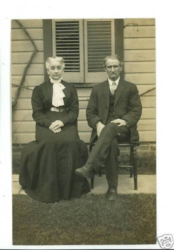 RPPC DISTINGUISHED MAN AND WOMAN SITTING OUTSIDE HOUSE