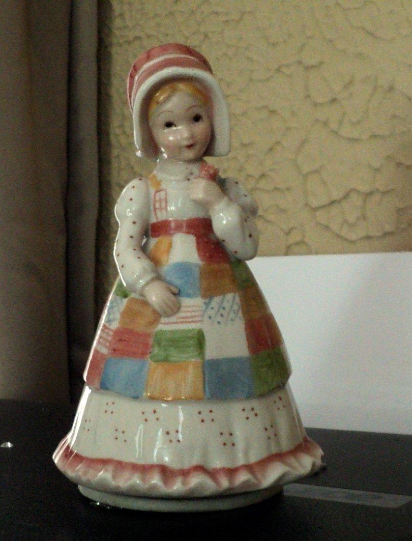 Little Pioneer Girl in Dress and Bonnet Holding Flower Music Box #400171