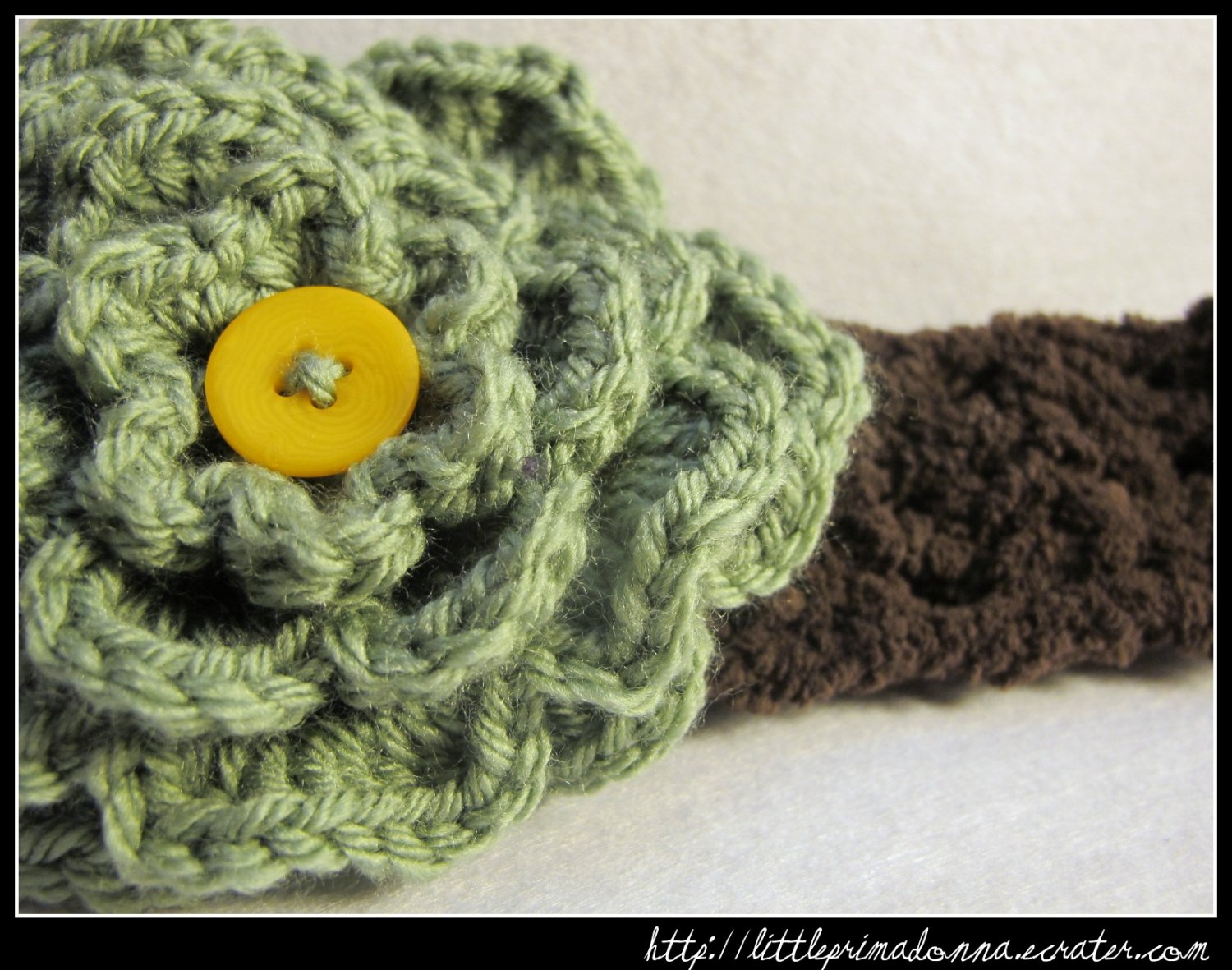 Crocheted headband with large green flower