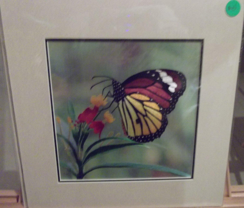 A butterfly near a few flowers