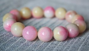 Peach jade bracelets, carved, about 13 mm beads, rubber bands strung together.