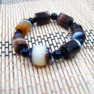 Natural colored agate cylindrical beads + black agate beads. The rubber band formed a bracelet.