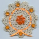 Crocheted doily with vintage orange colored plastic buttons